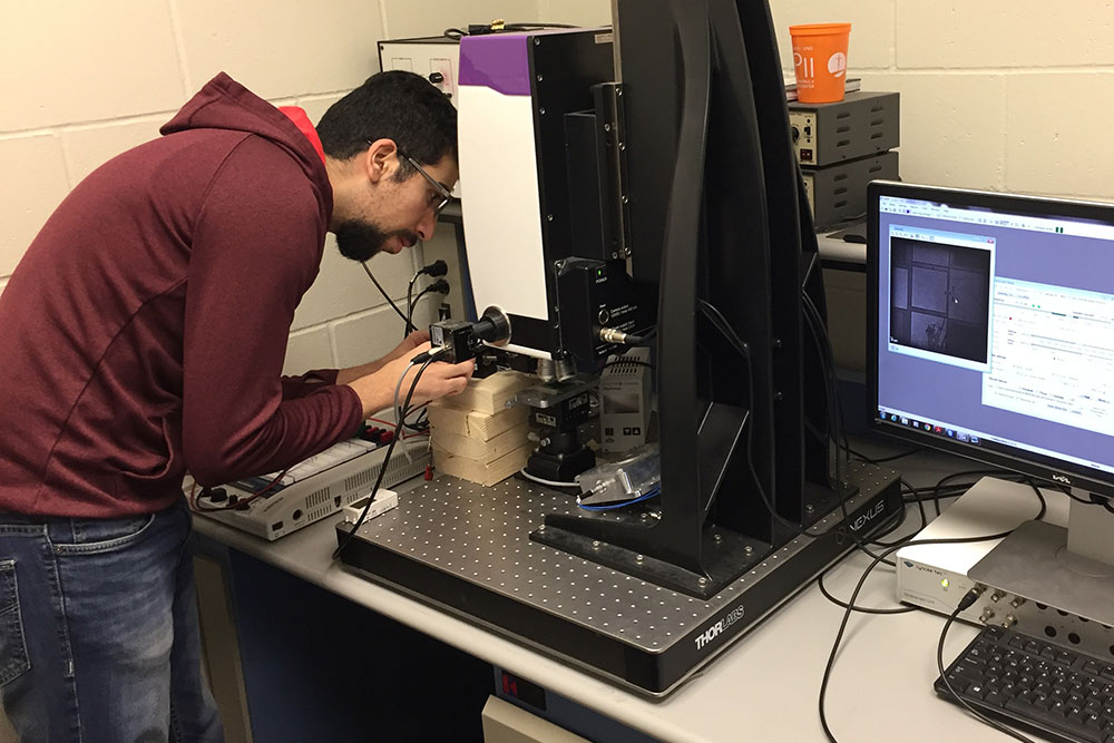 Mohamad H Hasan, a Ph.D. student in mechanical and materials engineering, works on a sample of soft material that has MEMS technology.