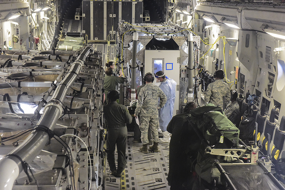 Air Force personnel work outside the transport isolation system (TIS) during a 2018 mission simulating the retrieval and care for patients exposed to an infectious disease.