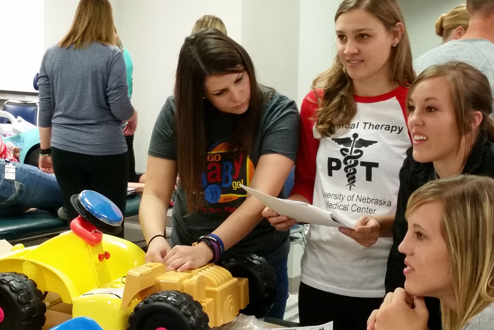 "Kate Watts (left), a graduate student in biological systems engineering, works with University of Nebraska Medical Center physical therapy students to retrofit a ""SpongeBob Square Pants""-themed car."