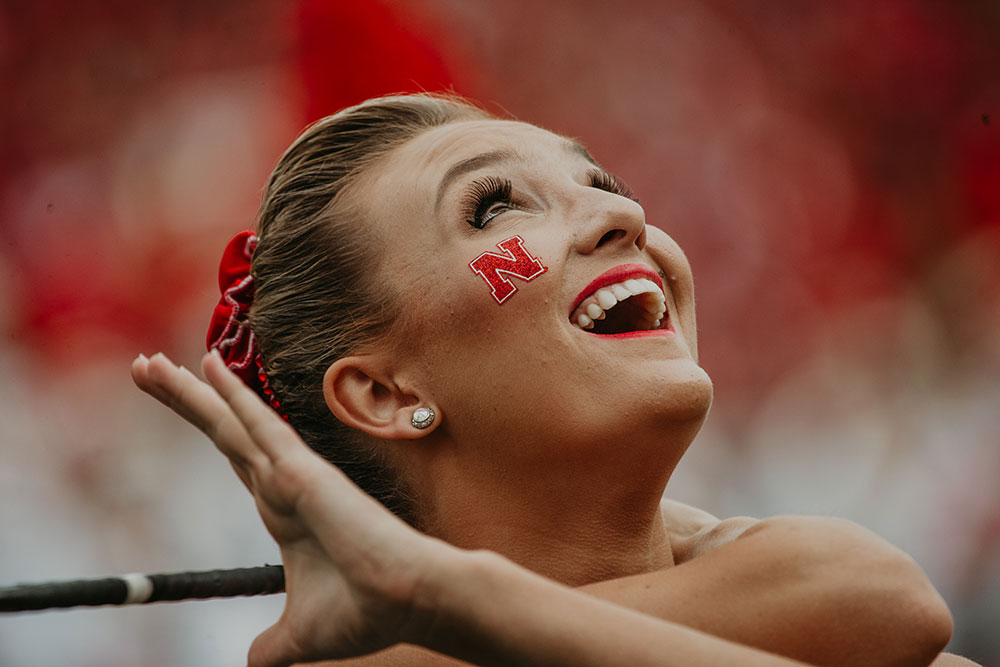 Kimberly Law, a freshman in chemical engineering from La Quinta, California, gazes skyward during a Cornhusker Marching Band performance on Sept. 8. (Photo by Justin Mohling)