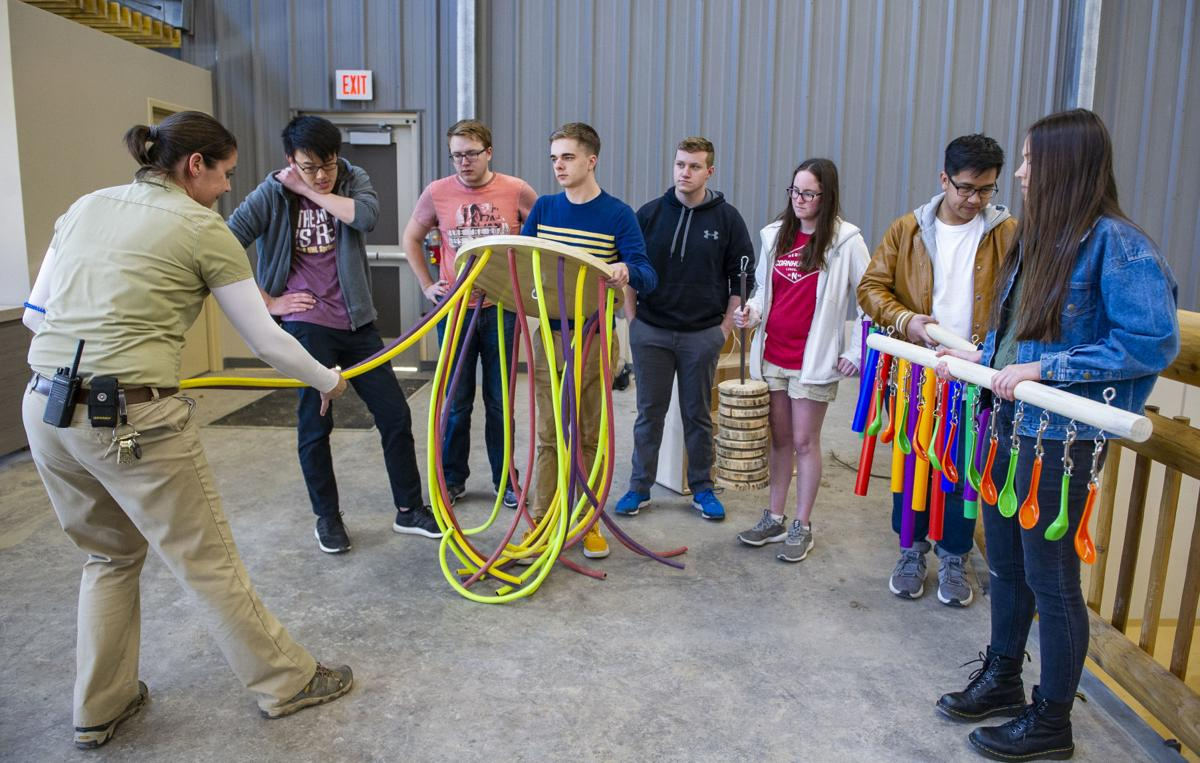 """Students in the Theme Park Design Group show their enrichment items to a Lincoln Children's Zoo employee. These """"toys"""" will help to keep the new zoo's new giraffes healthy and occupied. (Lincoln Journal Star photo)"""