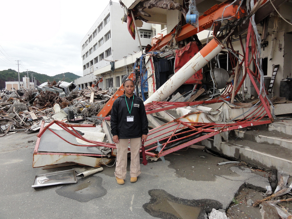 Norton stands in front of the canopy from a gas station, carried by tsunami waters and lodged into the entrance of a building