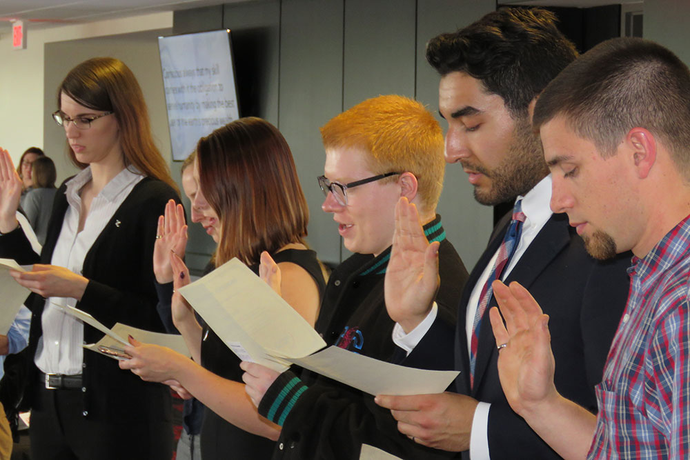 Students take the oath of initiation at the Order of the Engineer ceremony in the Memorial Stadium East Stadium Club Level. The ceremony was held after the Senior Design Showcase.
