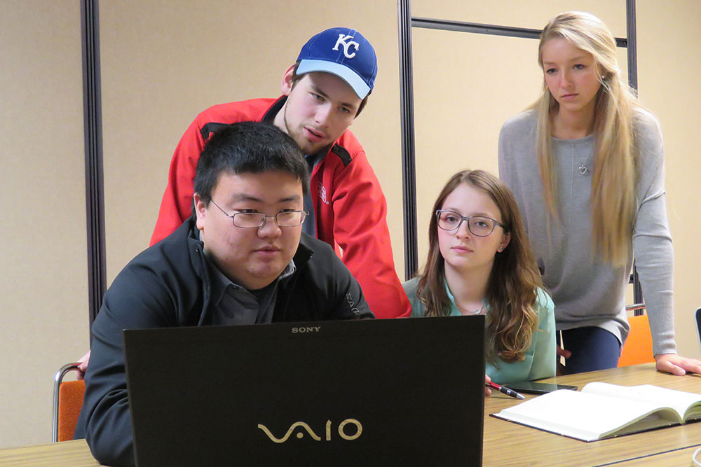 A team of biological systems engineering students -- (from left) Yuki Naoe, Doug Rowen, Merrill Brady and Kristina Zvolanek -- go over their design of the Pivot Panel, which would help VA hospital radiology technicians more safely assist patients off an X-ray table.