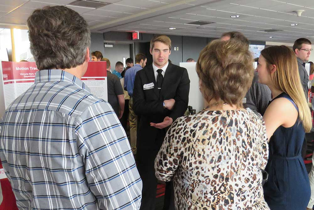 Biological Systems Engineering student Kevin Real discusses his team's project --Motion Tracking of Neonate Activity -- with guests at the Senior Design Showcase on April 21.