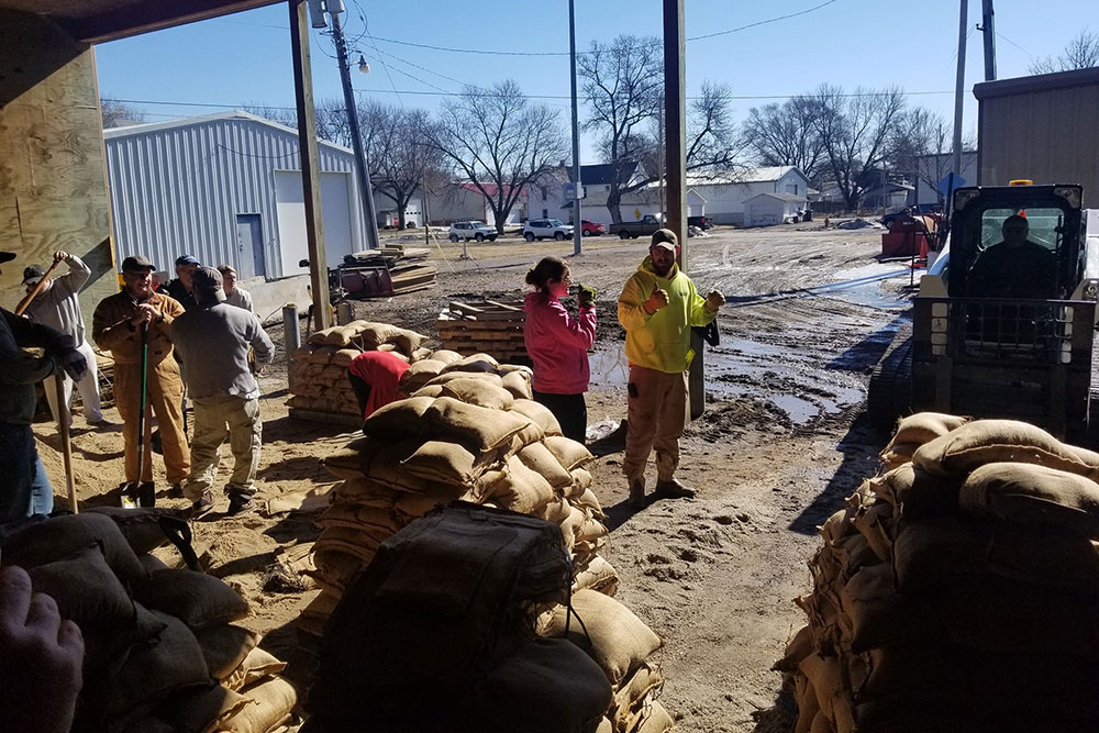 Volunteers take a break from making sandbags that would be used to bolster the levee along the Elkhorn River on the east edge of Waterloo.