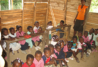 The old Flower of Hope School's classrooms had dirt floors and no chairs for the students.