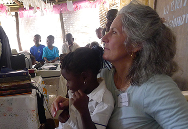 Martha Hoffman Goedert sits with one of the children who attend Flower of Hope.