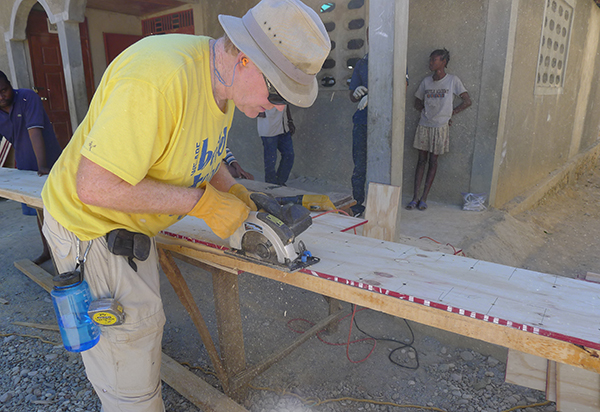 Durham professor James Goedert uses a circular saw to trim a wood joist for the roofing system at Flower of Hope school.