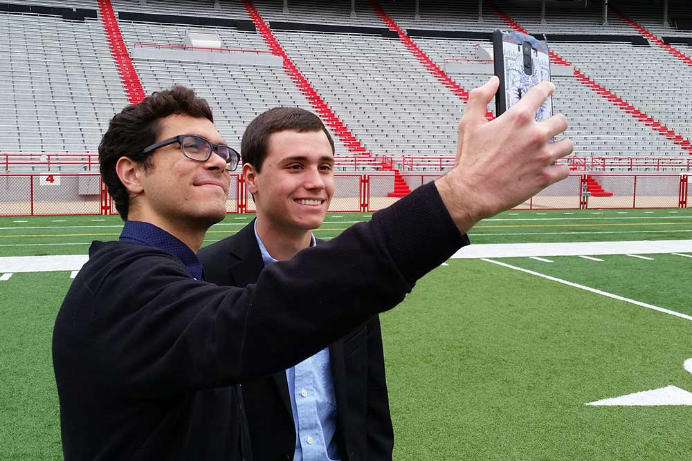 After taking part in the group picture on the field at Memorial Stadium, two engineering students take a selfie before returning to the Senior Design Showcase.