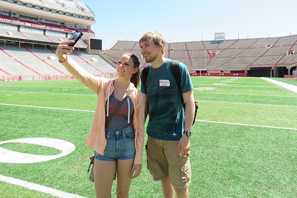 Two guests taking an engineering tour of Memorial Stadium stop to take a selfie on April 22 at the Senior Design Showcase.