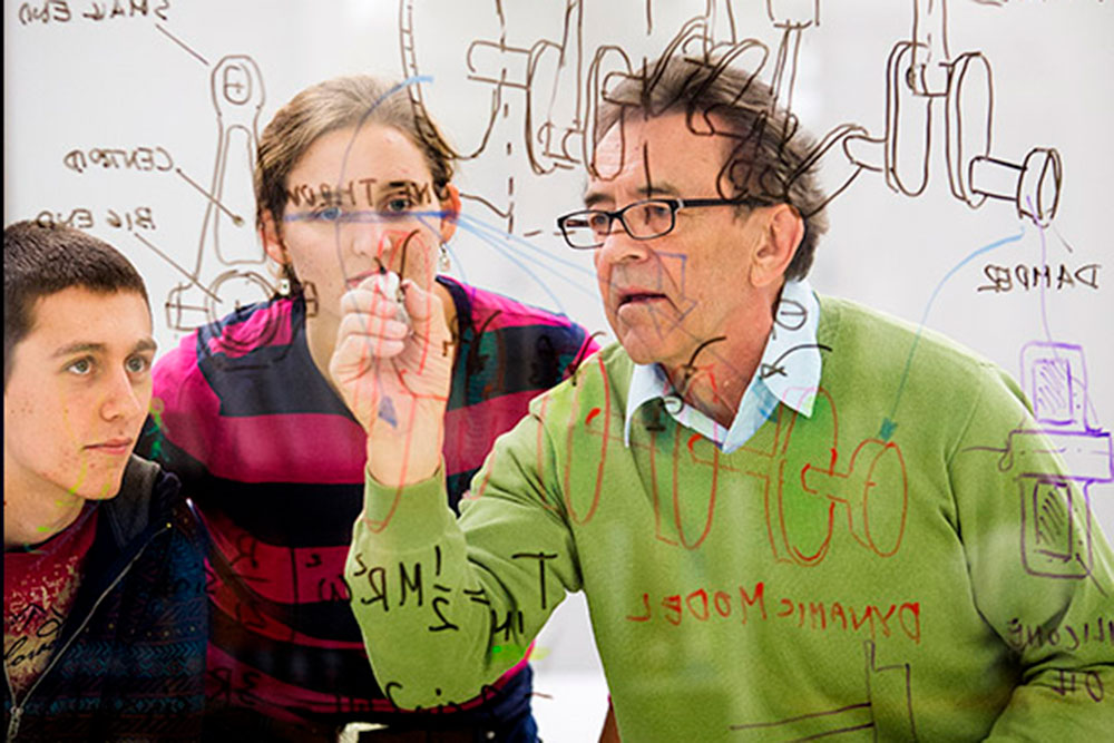 Wieslaw Szydlowski explains the design of an engine to students Matt Thompson (left) and Maggie Clay as it is drawn on the glass walls of the Olsson Room inside the Engineering Library in Nebraska Hall. (University Communication photo)