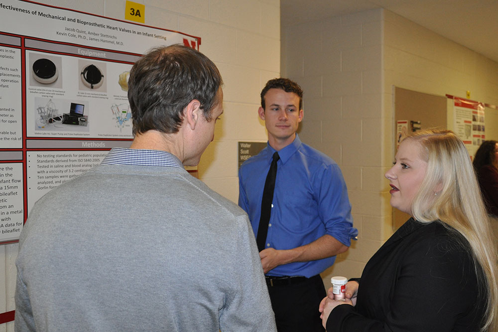 Amber Stettnichs (right) and Jacob Quint (center) explain their research to assistant professor Ryan Pedrigi.