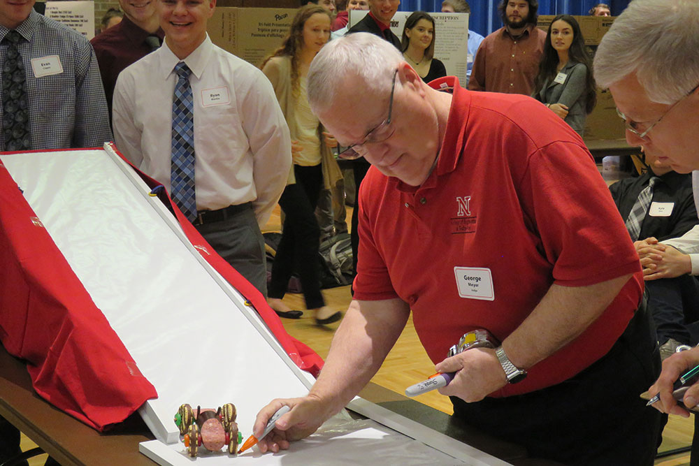 George Meyer, professor of biological systems engineering, measures the distance an edible vehicle covered after leaving a ramp during the Edible Vehicle competition on Dec. 5 at the Nebraska East Campus Union.