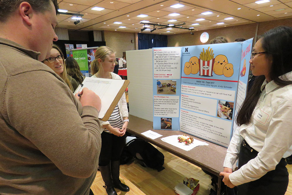 Becca Francis (left), Aly Schroeder and Linny Nguyen present their vehicle and poster to a judge during the Edible Vehicle competition on Dec. 5 at the Nebraska East Campus Union.