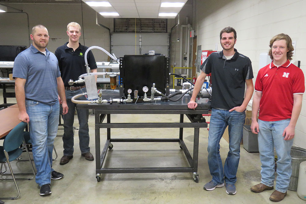 The biological systems engineering senior design capstone team -- (from left) John Nielsen, Luke Johnson, Aaron Steckly and Bennett Turner -- designed a system to help John Deere take damaging air bubbles out of the oil used in the hydraulic system of a tractor.