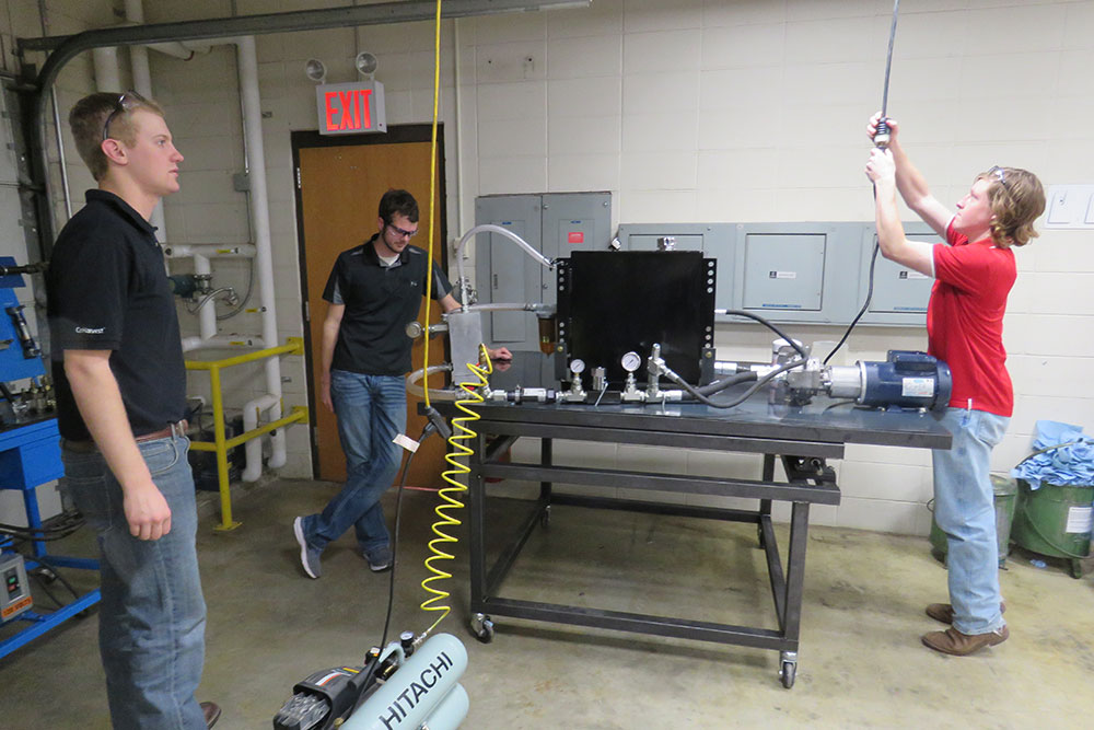 Luke Johnson (left), Aaron Steckly (center) and Bennett Turner prepare to test a filtration system their biological systems engineering capstone team designed to help John Deere take damaging air bubbles out of the oil used in the hydraulic system of a tractor.