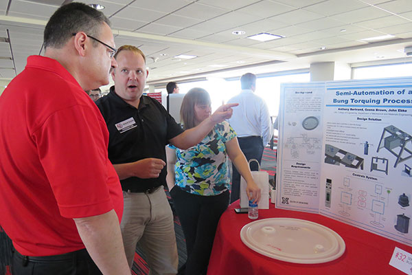 Mechanical and materials engineering student John Ebke explains his team's project - Semi-Automation of a Bung Torquing Process - to an interested guest April 22 at the Senior Design Showcase on the East Stadium Club Level of Memorial Stadium.