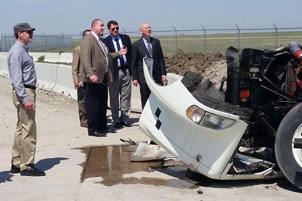 Nebraska Gov. Pete Ricketts (right) and Ron Faller, director of the Midwest Roadside Safety Facility, inspect the damage to the tractor-trailer's engine.