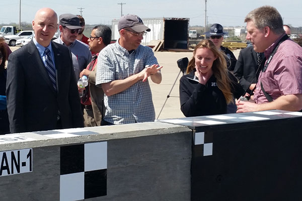 Nebraska Gov. Pete Ricketts (left), talks with Midwest Roadside Safety engineers Robert Bielenberg and Jennifer Schmidt and Manitoba Infrastructure and Transporation design engineer Andy Pankratz as the inspect the concrete barrier.