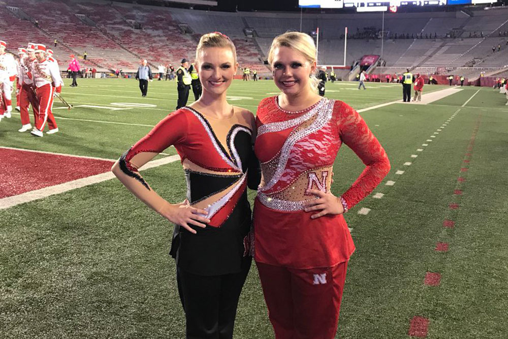 Kimberly Law (left), a freshman in chemical engineering, and senior Hannah Kollman are the featured twirlers this year with the Cornhusker Marching Band. (Photo from twitter.com/UNLTwirlers)