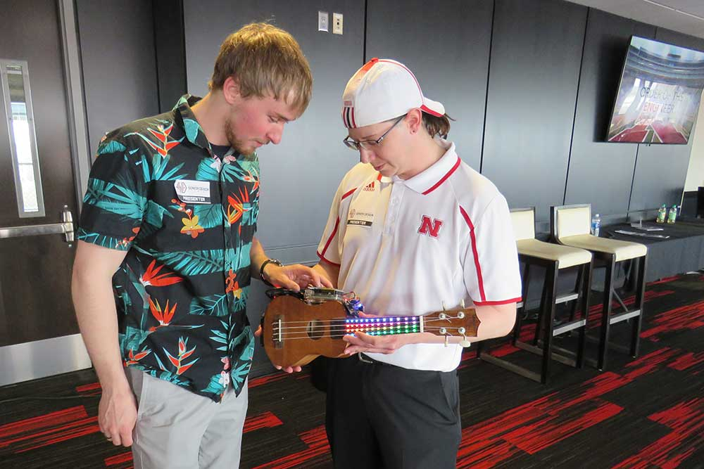 Zachary Kentner (left) and Andrew Tompkins examine the UkeBox, a device to teach people to play a ukulele, on April 21 at the Senior Design Showcase.
