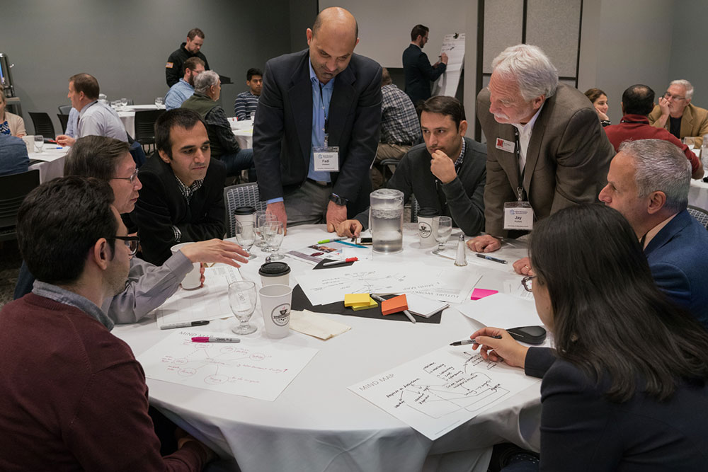 Fadi Alsaleem (standing left), assistant professor of architectural engineering, and Jay Puckett, director of The Durham School of Architectural Engineering and Construction, lead a discussion during the afternoon session Nov. 9 at the Smart Building and Internet of Things workshop.
