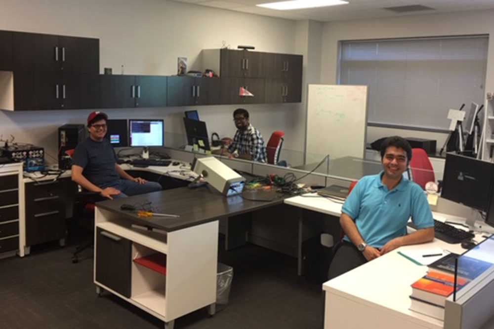 Carlos Brito (left) pauses with fellow researchers in the Advanced Telecommunications Engineering Laboratory in electrical and computer engineering.