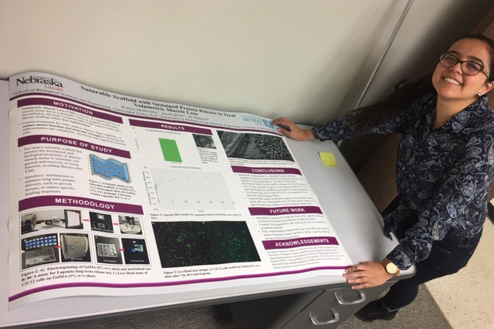 Evelyn Mollocana displays a poster of her research done in Laboratory for Innovative Microtechnologies and Biomechanics (LIMB) in mechanical and materials engineering.