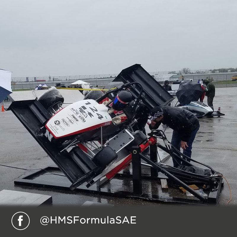 Facebook @HMSFormulaSAE (Formula race car being tipped at an angle during pre-race testing)