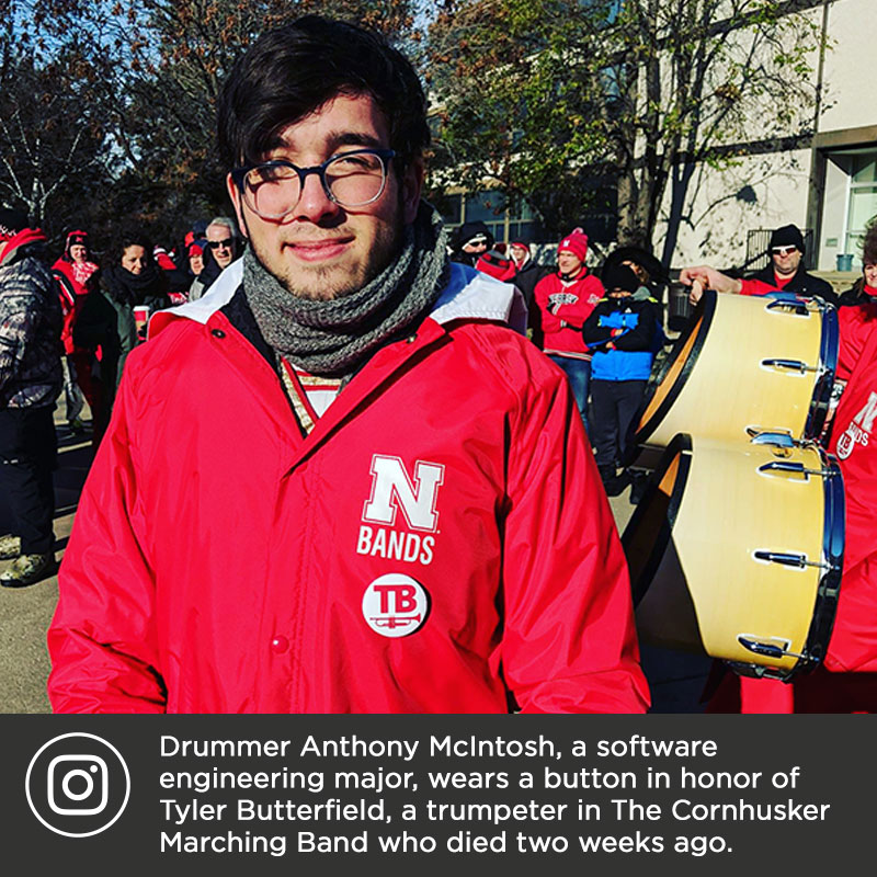 Drummer Anthony McIntosh, a software engineering major, wears a memorial button in honor of Tyler Butterfield, a trumpeter in The Cornhusker Marching Band who died in a car accident two weeks ago. The 300 members of the band will wear these buttons during today's game against Illinois.