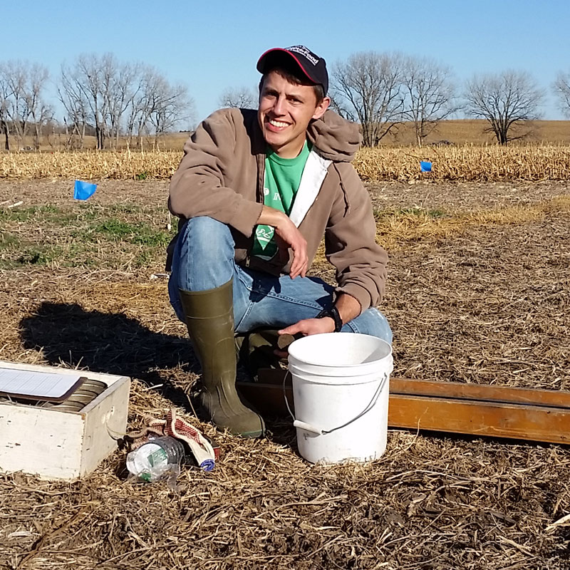 Burdette Barker squating in the middle of a field with a bucket and tools.