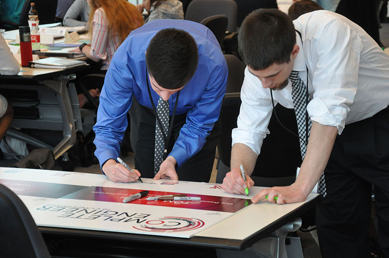 Several Nebraska Engineering students sign a large thank you card