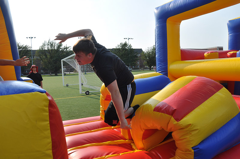 A students dives as he goes through the bounce house.