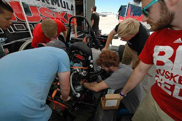 Husker Motorsports teammates stay out of the sun while they work to repair the clutch on the car before Friday's autocross competition during the Formula SAE Lincoln event at Lincoln Airpark June 17-20. For a look at Nebraska Engineering teams in competitions,