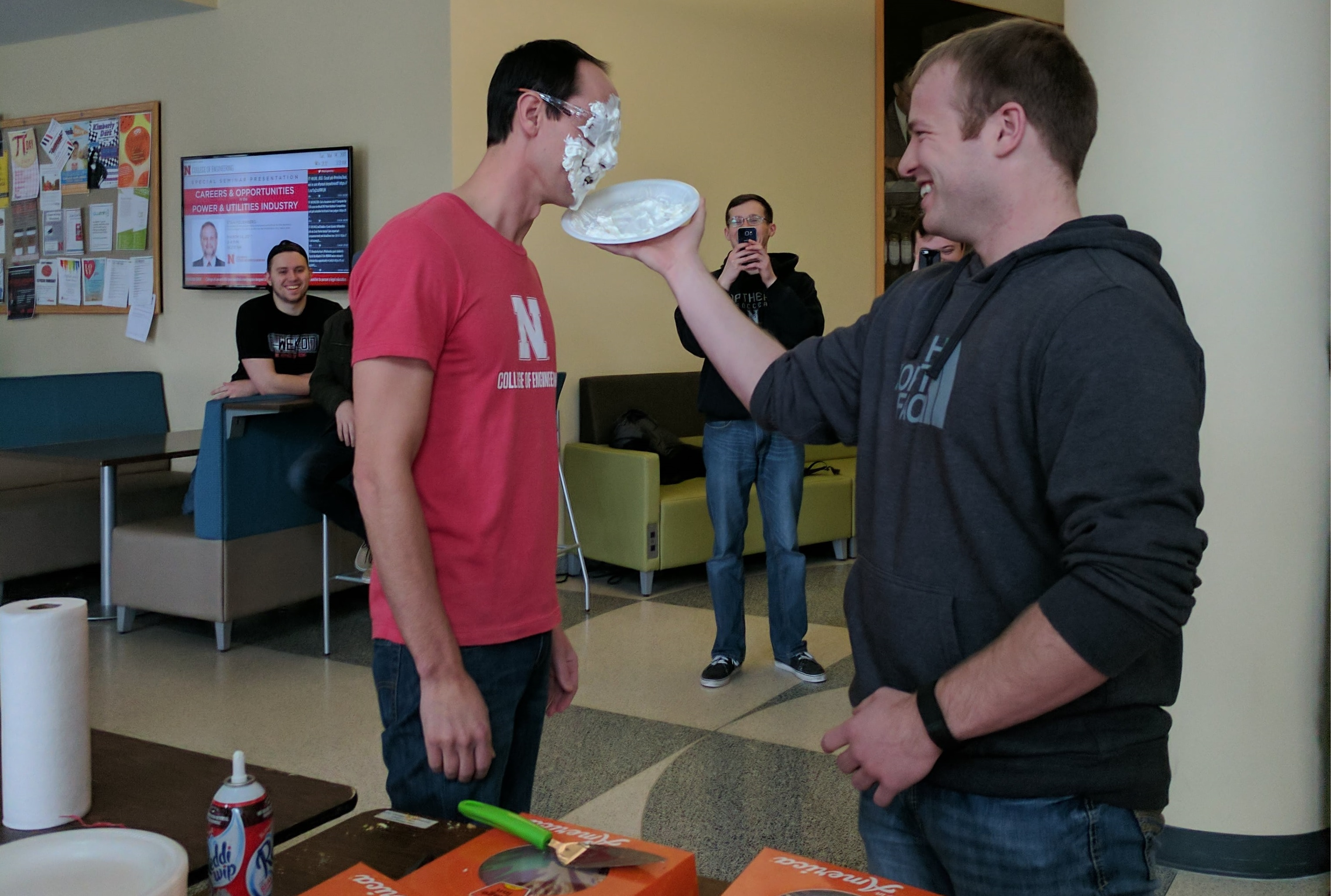 A member pie-ing Dr. Flodman on Pi Day