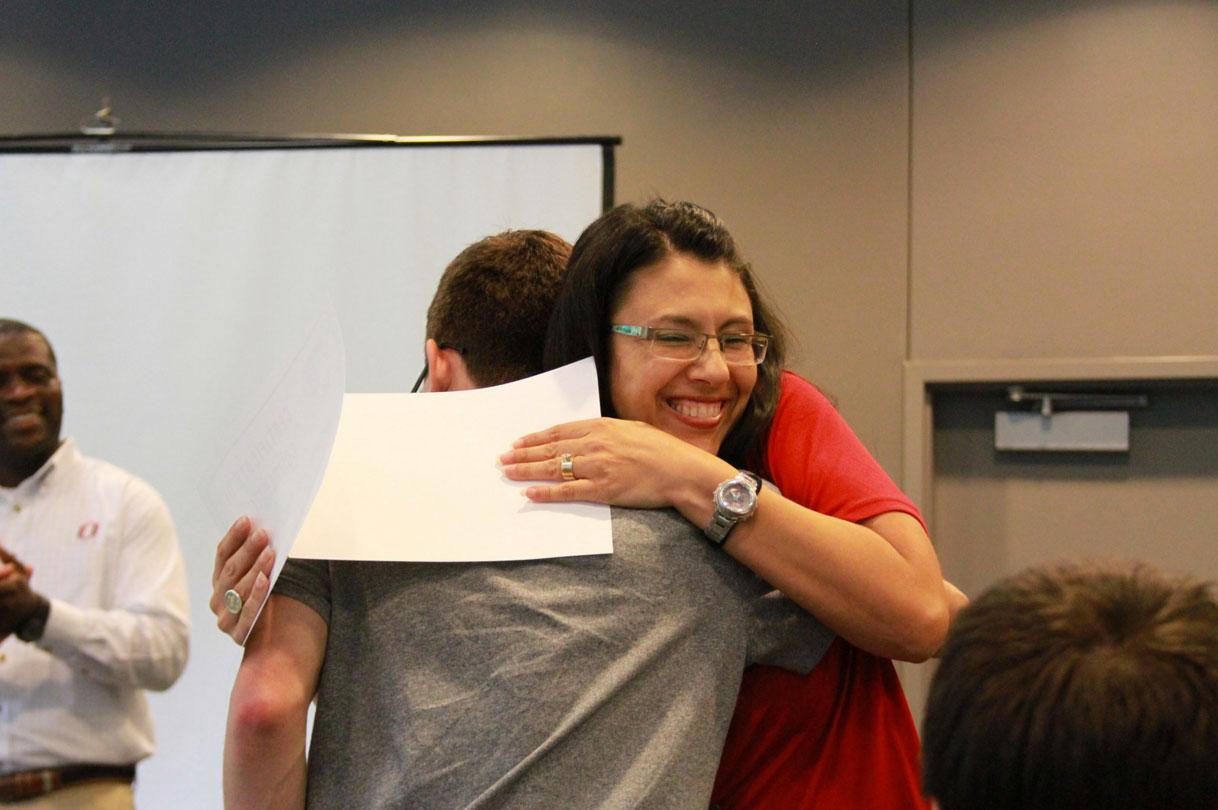 A happy award winner receives a hug at the 2015 Math Prep Academy