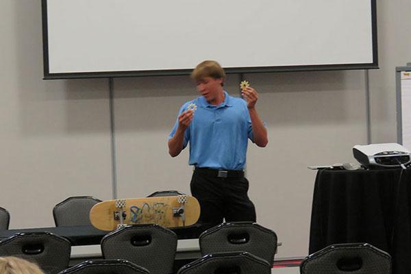 Kearney graduate, Jonah Staab demonstrates his PLTW EDD invention, special skate wheels he designed.