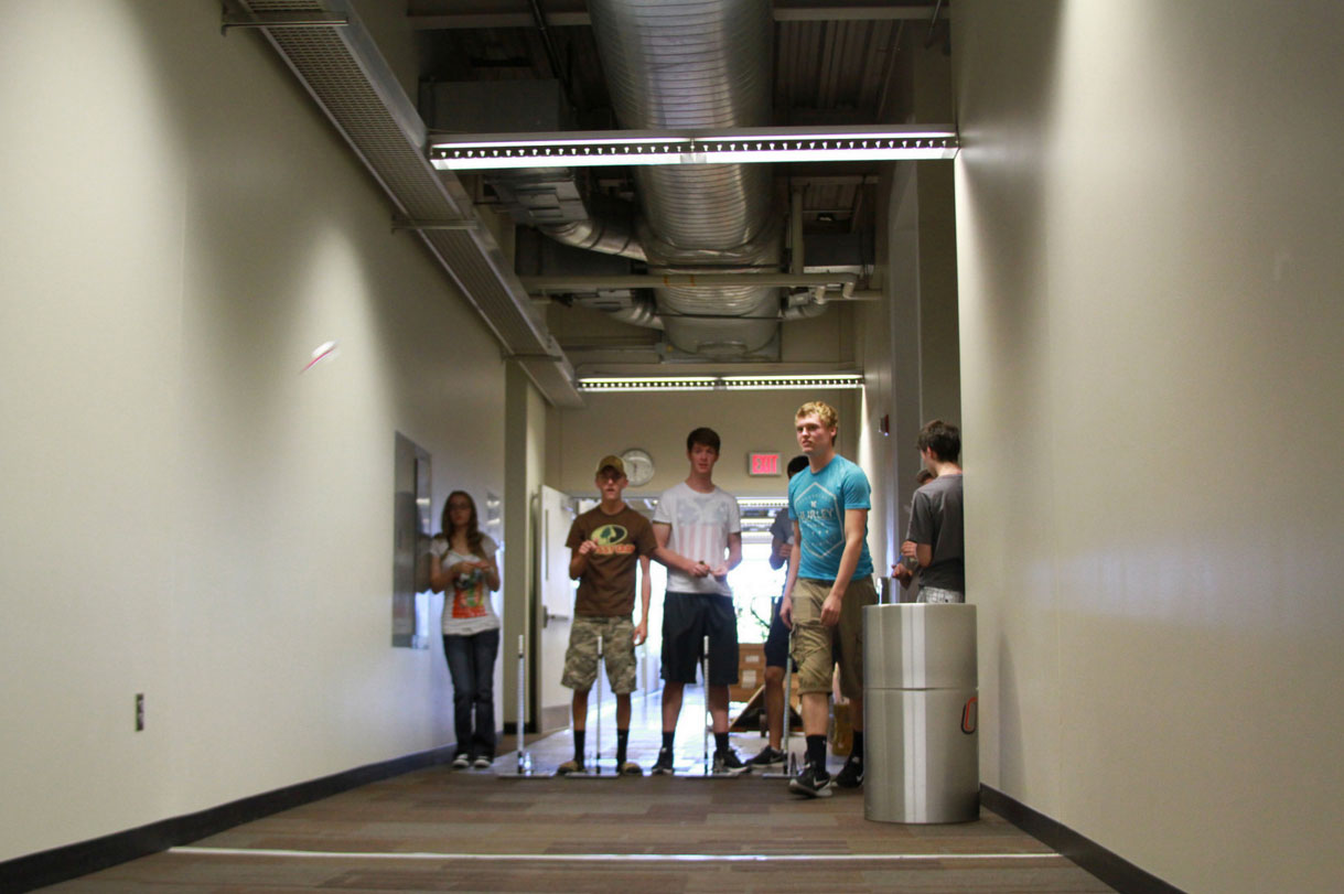 Student teams perform tests in a hallway