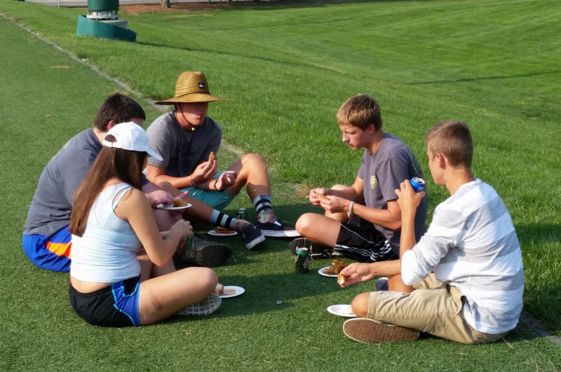 Students sit together in a huddle enjoying their meal