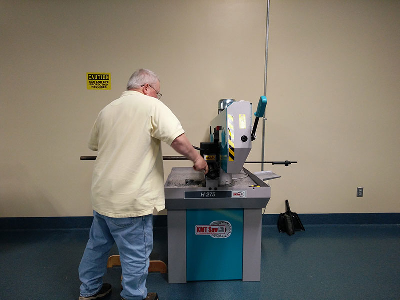 Worker using a saw inside the Design and Fabrication Lab