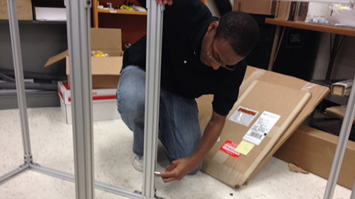 Blake Stewart begins assembling the frame to hold the 2014 UNL Microgravity Team's project while it travels (including parabolic test flights).
