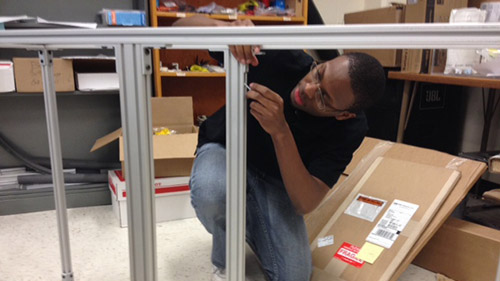 Blake Stewart continues assembling the frame to hold the UNL Microgravity Team's 2014 project while it travels (including parabolic test flights).