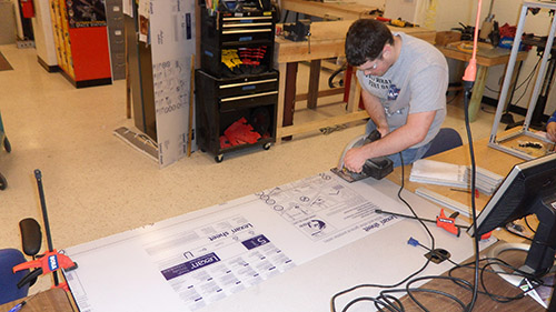 Ethan Monhollon works on panels for the frame assembly to hold the 2014 UNL Microgravity Team project.