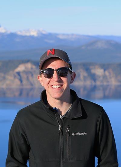 UNL Civil Engineering Alumni Bryan Kubitschek posing in front of a lake and mountain scene.