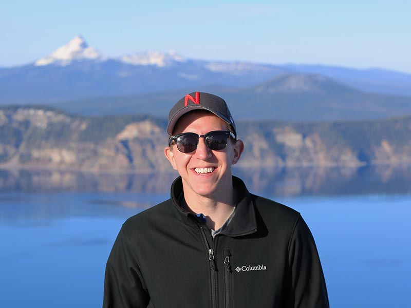 Bryan Kubitschek standing in front a lake and mountains.