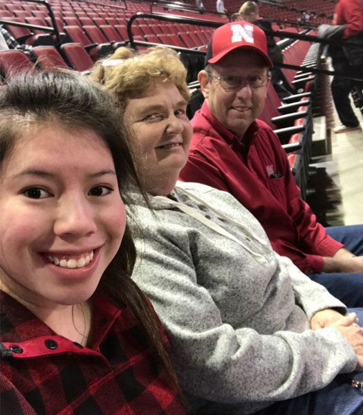 Emily Ritzdorf sitting with her parents at Pinnacle Bank Arena for a Huskers basketball game.
