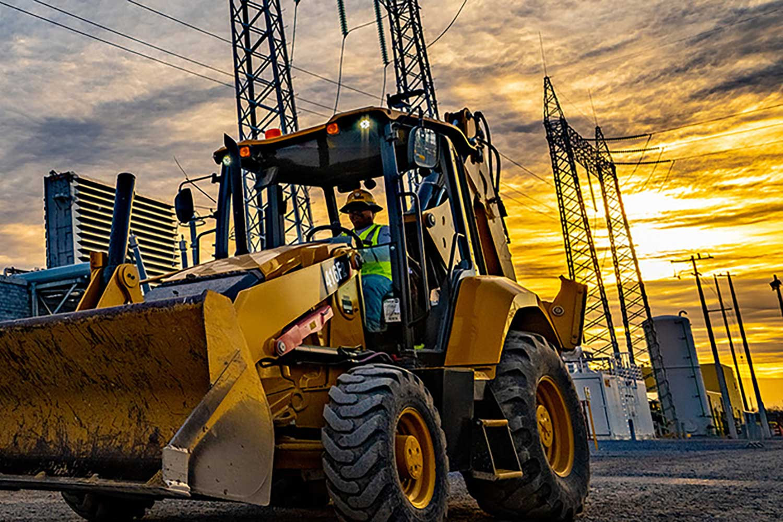 Kiewit employee driving heavy equipment across a construction site.