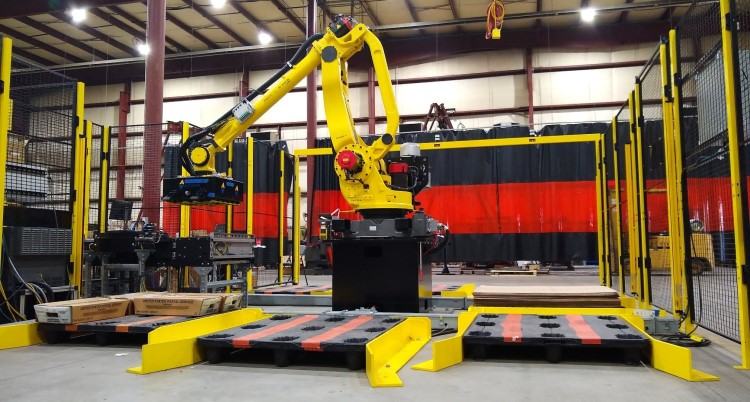 CapStone Technologies's Palletizer. This robotic arm is very large and is bright yellow, and puts items in pallets.