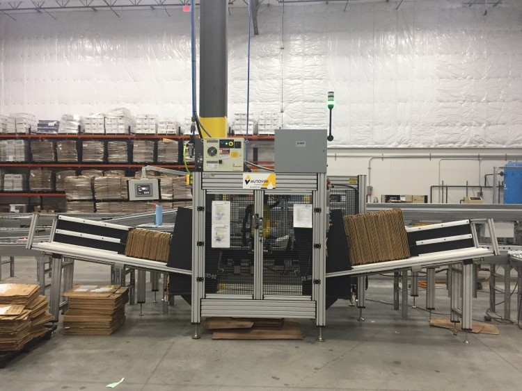 The CapStone Technologies' Sleever. This machine, approximately 4-5' tall, appears to sleeve sets of flattened cardboard boxes together on two ends, with its core mechanisms protected by a cage in the middle.